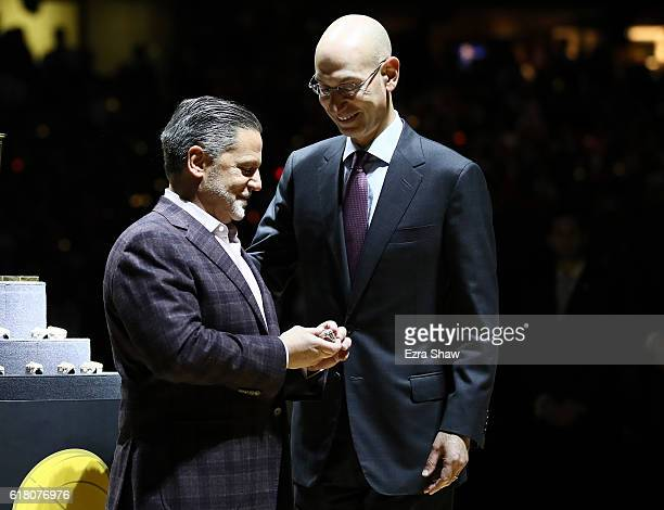 Owner Dan Gilbert of the Cleveland Cavaliers speaks to NBA Commissioner Adam Silver as he receives his championship ring before a game against the...
