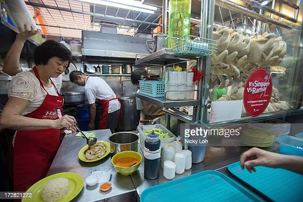 Owner Foo Kui Lian of the Tian Tian chicken rice stall pours sauce at the Maxwell Food Centre on July 5 2013 in Singapore Celebrity chef Gordon...