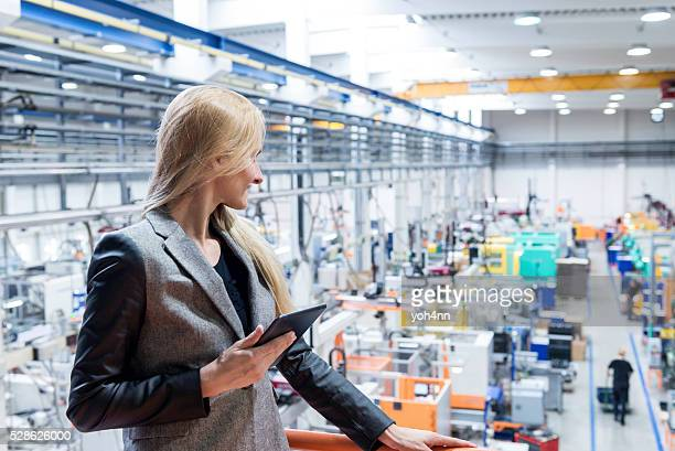 Owner holding tablet and examining production in factory