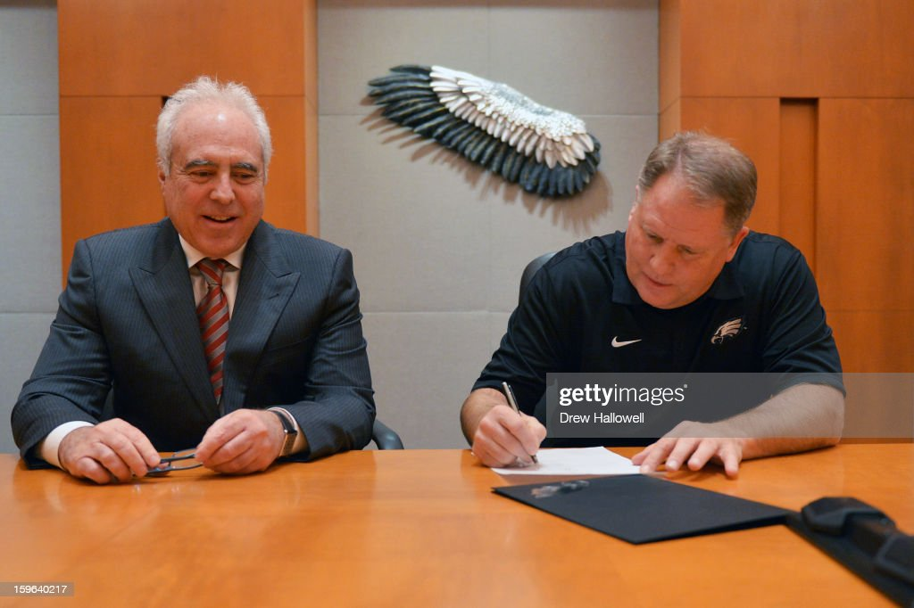 Owner <a gi-track='captionPersonalityLinkClicked' href=/galleries/search?phrase=Jeffrey+Lurie&family=editorial&specificpeople=221287 ng-click='$event.stopPropagation()'>Jeffrey Lurie</a> (L) of the Philadelphia Eagles watches as new head coach <a gi-track='captionPersonalityLinkClicked' href=/galleries/search?phrase=Chip+Kelly&family=editorial&specificpeople=6161242 ng-click='$event.stopPropagation()'>Chip Kelly</a> signs a contract at the NovaCare Complex on January 17, 2013 in Philadelphia, Pennsylvania.