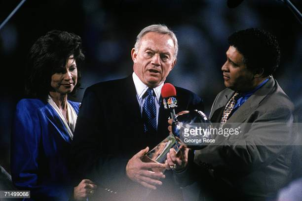 Owner Jerry Jones of the Dallas Cowboys holds the Lombardi Trophy as he talks with sports commentator Greg Gumbel after Super Bowl XXX against the...