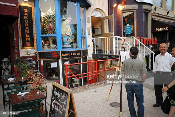 Owner Jonathan Cho stands outside his restaurant Sakuramen Ramen Bar talking with customers on Tuesday July 5th 2012
