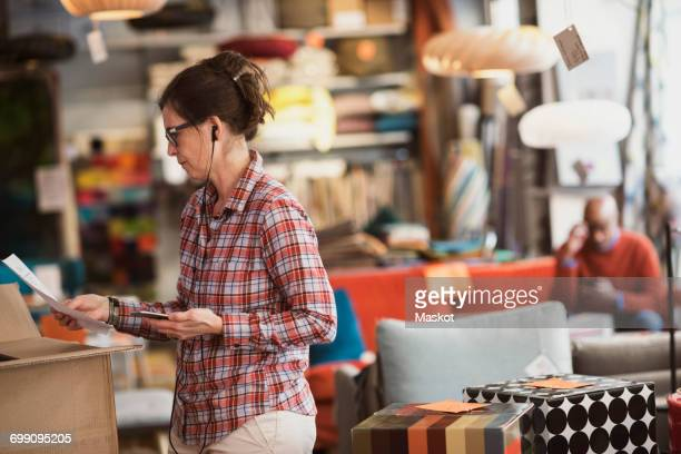Owner listening music through phone while reading document at store
