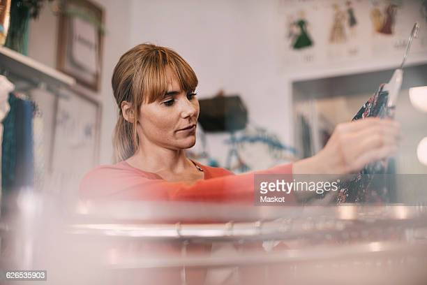 Owner looking at dress while standing at thrift store