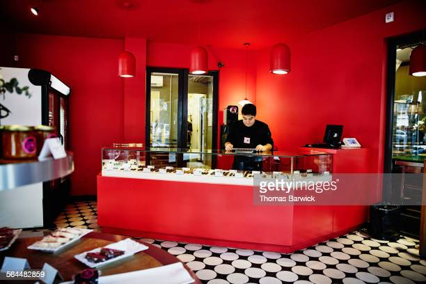 Owner of chocolate shop at display counter