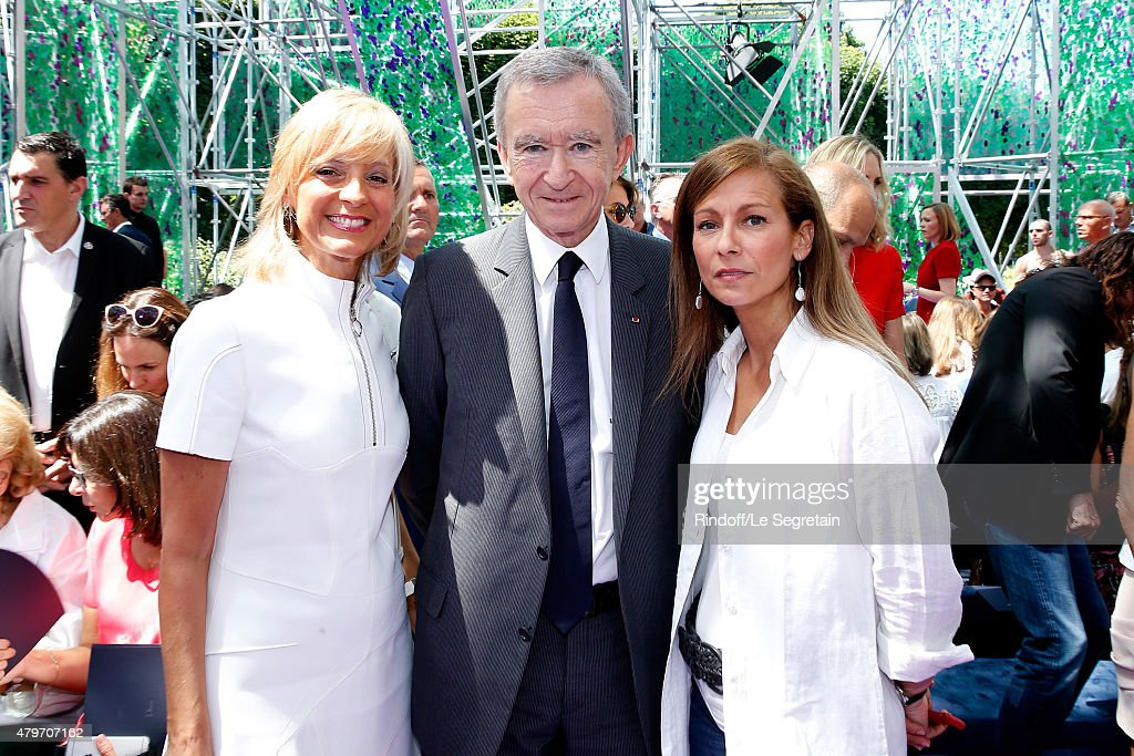 Owner of LVMH Luxury Group <a gi-track='captionPersonalityLinkClicked' href=/galleries/search?phrase=Bernard+Arnault&family=editorial&specificpeople=214118 ng-click='$event.stopPropagation()'>Bernard Arnault</a> standing between his wife <a gi-track='captionPersonalityLinkClicked' href=/galleries/search?phrase=Helene+Arnault&family=editorial&specificpeople=718530 ng-click='$event.stopPropagation()'>Helene Arnault</a> (L) and Miss Manuel Valls, Violonist <a gi-track='captionPersonalityLinkClicked' href=/galleries/search?phrase=Anne+Gravoin&family=editorial&specificpeople=8536985 ng-click='$event.stopPropagation()'>Anne Gravoin</a> (R) attend the Christian Dior show as part of Paris Fashion Week Haute-Couture Fall/Winter 2015/2016 on July 6, 2015 in Paris, France.
