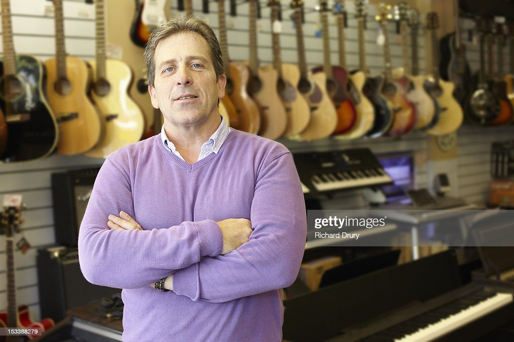 Owner of music shop in his store : Stock Photo