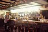 Owner standing beside bar in 16th Century Scottish pub, Portrait