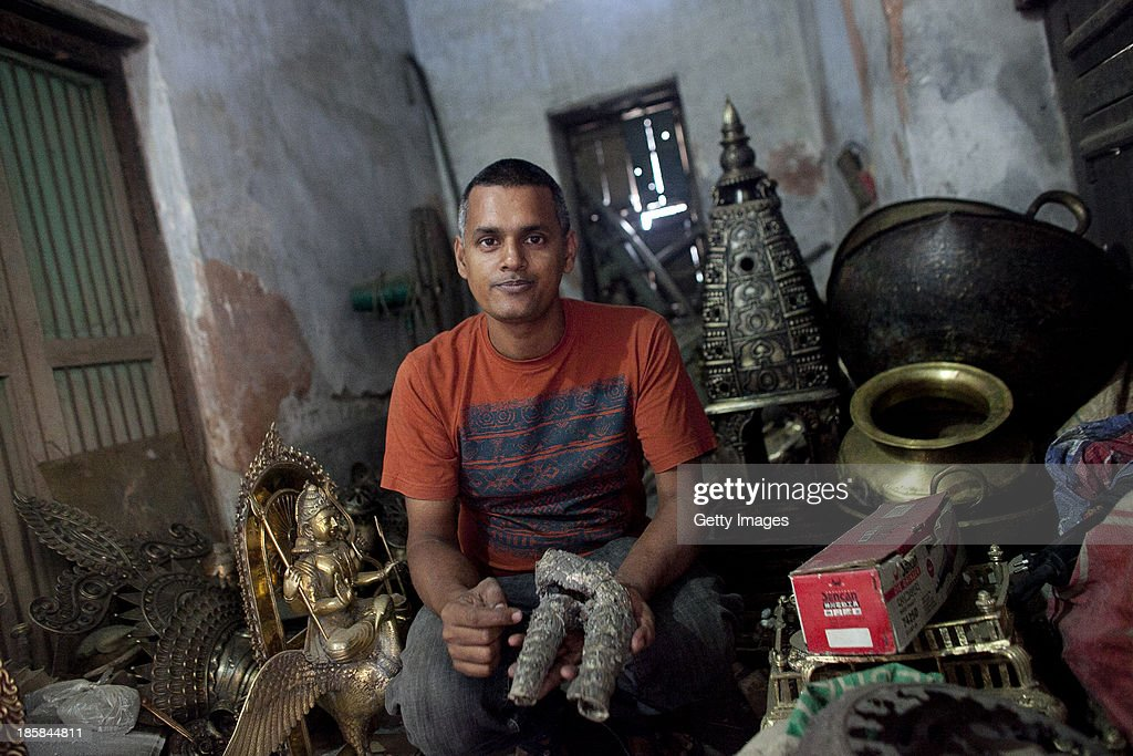 Owner Sukanta Banik is seen in the showroom at Dhamrai Metal Crafts on October 5, 2013 in Dhaka, Bangladesh. Banik creates bronze sculptures in the art of 'lost wax casting.' The business has been in his family for 200 years. The pieces are first molded in wax, then encased in clay, then baked in the oven, after which metal is poured into the mold. One piece can take up to 10 months to make. The business is suffering because most of these items he creates can now be mass produced in plastic, and as a Hindu artist working in Islamic Bangladesh, the 'depiction of all humans and animals are discouraged by the majority religion.' Recently it took a year and a half to send an order overseas, when Bangladeshi customs held his work in hopes for a bribe.