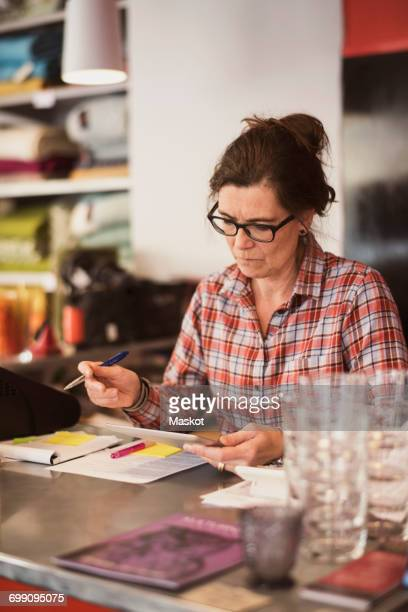 Owner using digital tablet while making notes at checkout counter in store