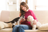 Little dog maltese and black and white cat sitting with owner on the sofa in home