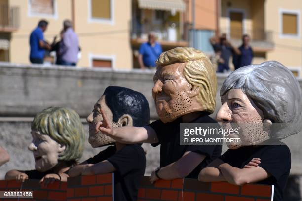 Oxfam activists wearing masks of the leaders of the G7 summit German Chancellor Angela Merkel Japanese Prime Minister Shinzo Abe US President Donald...