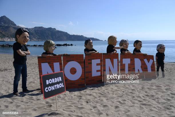 Oxfam activists wearing masks of the leaders of the G7 summit Canadian Prime Minister Justin Trudeau German Chancellor Angela Merkel Japanese Prime...