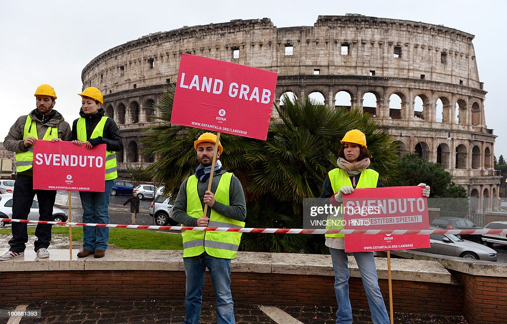 Oxfam members demonstrate holding 'Land Grab' and 'Sell Off ' banners in front of the ancient Colisseum in Rome on February 7, 2013. Oxfam steps up its campaign across the world on grabbing famous landmarks, to end land grabs that violate the rights of the world's poorest people.