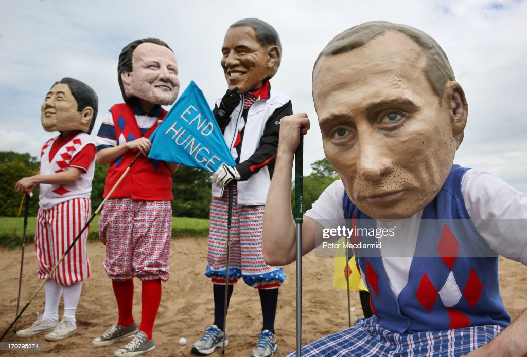 Oxfam volunteers wearing caricature heads depicting (L-R) Japanese Prime Minister Shinzo Abe, British Prime Minister David Cameron, US President Barack Obama and Russia's President <a gi-track='captionPersonalityLinkClicked' href=/galleries/search?phrase=Vladimir+Putin&family=editorial&specificpeople=154896 ng-click='$event.stopPropagation()'>Vladimir Putin</a> pose in golf clothing as part of their End Hunger campaign photocall on June 18, 2013 in Enniskillen, Northern Ireland. The G8 summit, hosted by UK Prime Minister David Cameron, is expected to discuss tax avoidance issues on it's final day.