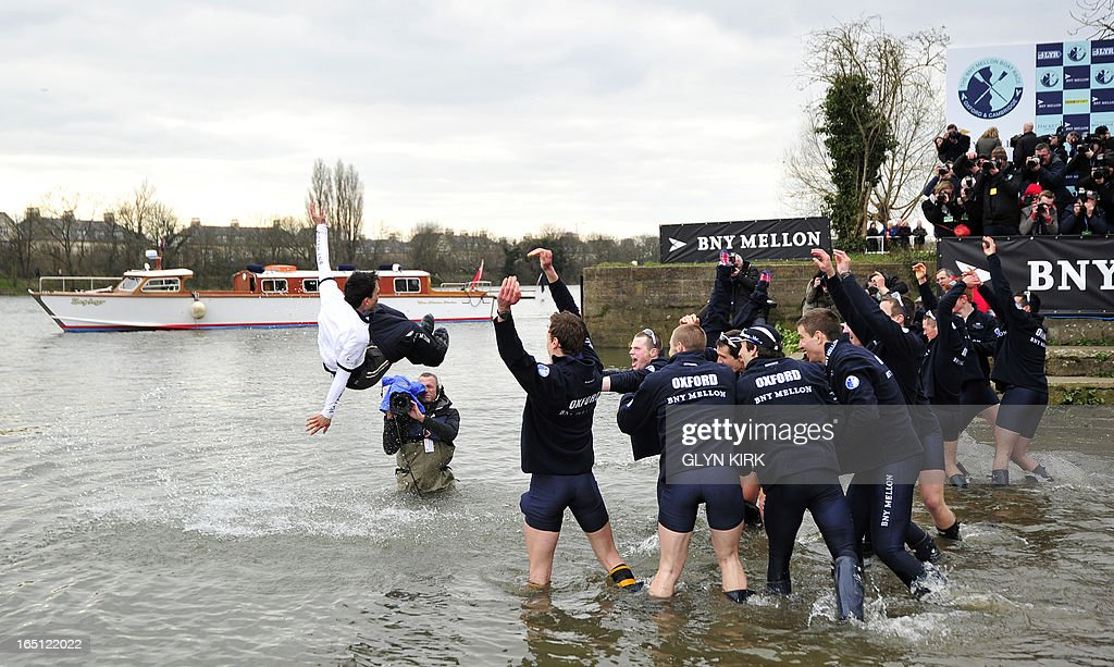 Oxford rowers celebrate by throwing their USColombian cox Oskar Zorrilla into the river after Oxford's victory over Cambridge in the 159th annual...