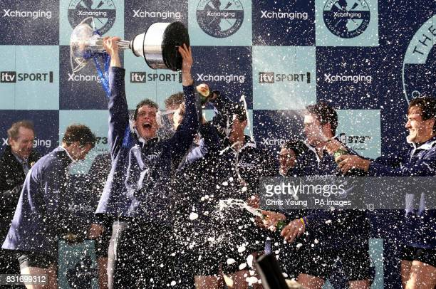 Oxford's president Barney Williams lifts the trophy as he celebrates with the crew after winning against Cambridge in the 152nd University Boat Race...