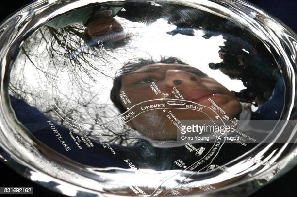 Oxford's President Barney Williams views his reflection and that of the Cambridge President Tom Edwards in the Boat Race Trophy following the...