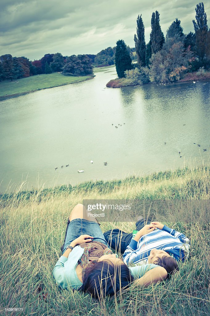 Oxfordshire, England, Young woman and boy resting by the lake : Stock Photo