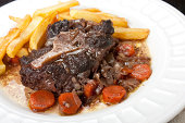 Oxtail stew with wine and vegetables accompanied by home  fries