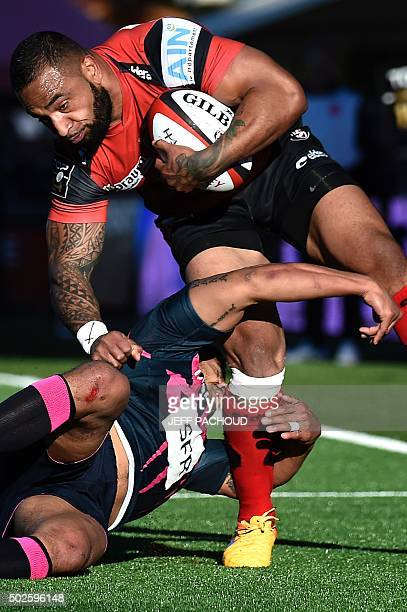 Oyonnax' Tongan centre Fetu'u Vainikolo is tackled by Stade Francais Paris' Australian scrumhalf Will Genia during the French Top 14 rugby union...