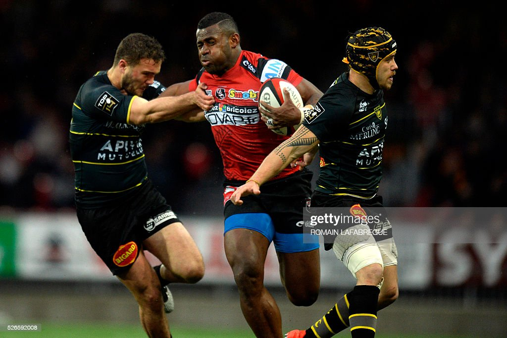 Oyonnax's Fiji winger Uwanakoro Tawalo (C) runs with the ball despite of La Rochelle's French number eight Kevin Gourdon (L) and La Rochelle's French winger Gabriel Lacroix during the French Top 14 Rugby Union match between Union Sportive Oyonnax Rugby (USO) and Atlantique Stade Rochelais (ASR) on April 30, 2016 at the Charles-Mathon stadium in Oyonnax, central eastern France. Oyonnax won the match 17-16. / AFP / ROMAIN