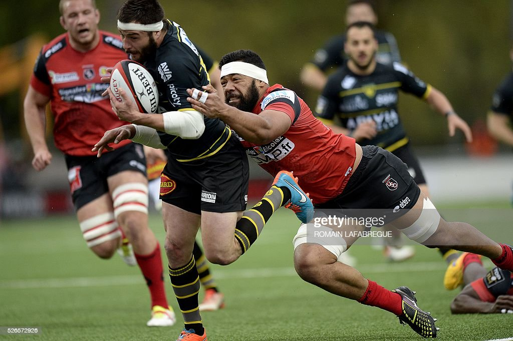 Oyonnaxs Tongan number 8 Viliami Ma'afu (R) dives to tackle La Rochelle's French centre Pierre Aguillon (L) during the French Top 14 Rugby Union match between Oyonnax and La Rochelle on April 30, 2016 at the Charles-Mathon stadium in Oyonnax, central-eastern France. / AFP / ROMAIN