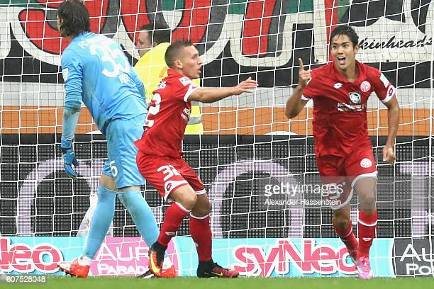 oYoshinori Muto of Mainz celebrates scoring the 3rd team goal with his team mate Pablo De Blasis whilst Marwin Hitz keeper of Augsburg reacts during...