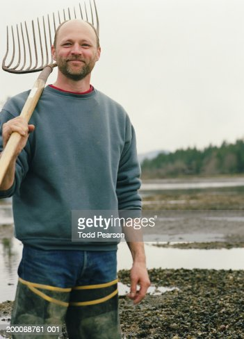 Oyster farmer with rake standing by oyster bed, portrait : Stock Photo