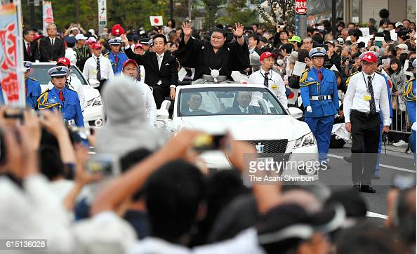 Ozeki Goeido waves to fans during the victory parade to celebrate his win of the Grand Sumo Autumn Tournament on October 16 2016 in Meyagawa Osaka...