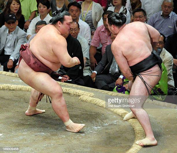 Ozeki Kisenosato pushes Russian wrestler Aran whose real name is Alan Gabaraev to win during day eleven of the Grand Sumo Summer Tournament at...