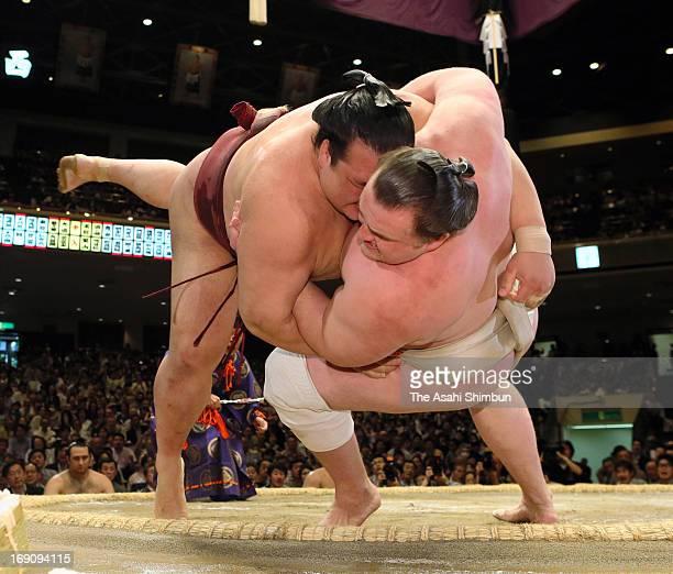 Ozeki Kisenosato throws Estonian Sumo wrestler Baruto whose real name is Kaido Hoovelson to win during day eight of the Grand Sumo Summer Tournament...