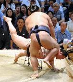 Ozeki Kisenosato throws Mongolian yokozuna Hakuho to win during day fourteen of the Grand Sumo Nagoya Tournament at the Aichi Prefecture Gymnasium on...
