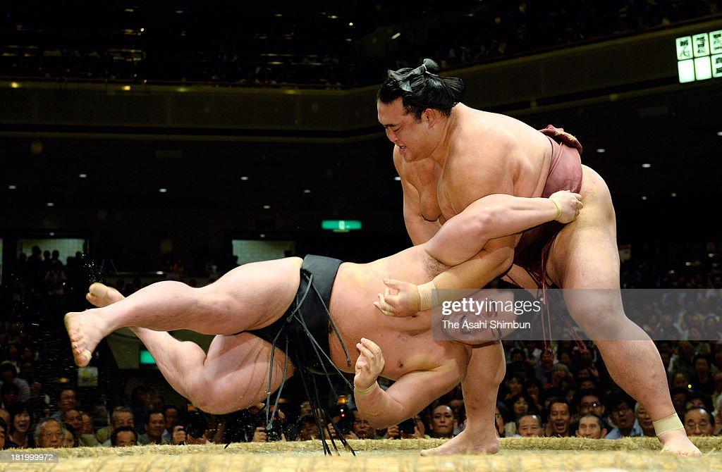 Ozeki Kisenosato (R) throws Mongolian yokozuna Harumafuji, whose real name is Altangadasyn Khuchitbaatar during day twelve of the Grand Sumo Autumn Tournament at Ryogoku Kokugikan on September 26, 2013 in Tokyo, Japan.