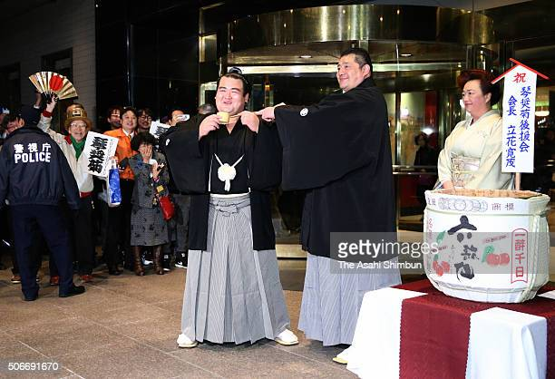 Ozeki Kotoshogiku is poured sake by his stable master Sadogatake to celebrate after winning the tournament during day fifteen of the Grand Sumo New...