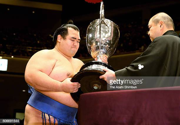 Ozeki Kotoshogiku receives the trophy by the Japan Sumo Association President and stable master Hakkaku during day fifteen of the Grand Sumo New Year...