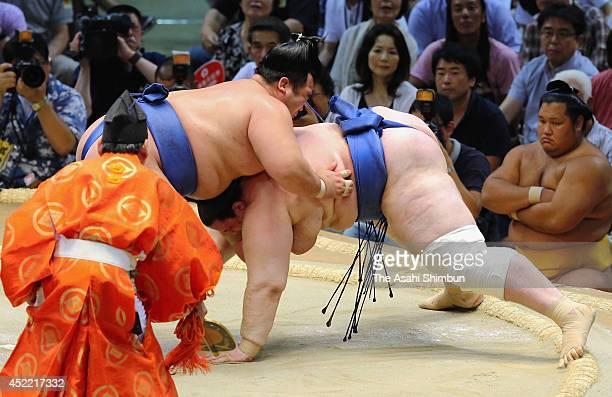 Ozeki Kotoshogiku throws Aoiyama to win during day three of the Grand Sumo Nagoya Tournament at Aichi Prefecture Gymnasium on July 15 2014 in Nagoya...
