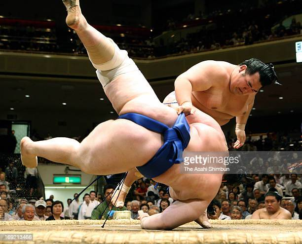 Ozeki Kotoshogiku throws Bulgarian sumo wrestler Aoiyama whose real name is Daniel Ivanov to win during day ten of the Grand Sumo Summer Tournament...