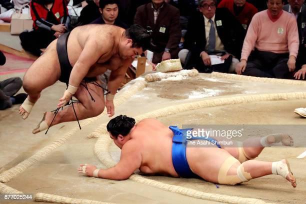 Ozeki Takayasu jumps to fend off as he throws Kotoshogiku to win during day ten of the Grand Sumo Kyushu Tournament at Fukuoka Convention Center on...