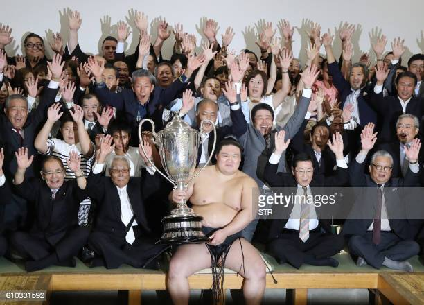 TOPSHOT Ozekiranked wrester Goeido holding the champion trophy of the Autumn Grand Sumo Tournament celebrates his victory with supporters in Tokyo on...