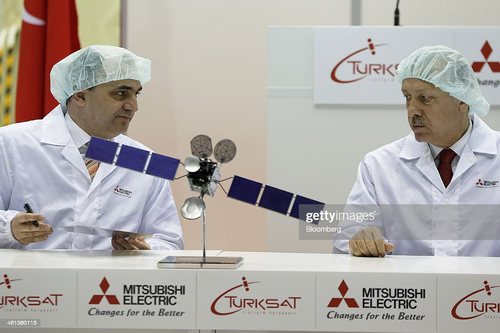 Ozkan Dalbay, chief executive officer of Turksat AS, left, looks towards <a gi-track='captionPersonalityLinkClicked' href=/galleries/search?phrase=Recep+Tayyip+Erdogan&family=editorial&specificpeople=213890 ng-click='$event.stopPropagation()'>Recep Tayyip Erdogan</a>, Turkey's prime minister, while signing a memorial panel as they sit behind a 1:80 scale model of Turksat AS's Turksat-4A communications satellite, manufactured by Mitsubishi Electric Corp., during a ceremony at the company's satellite production facility at Kamakura Works in Kamakura, Kanagawa Prefecture, Japan, on Wednesday, Jan. 8, 2014. Turksat AS is Turkey's state-owned satellite operator. Photographer: Kiyoshi Ota/Bloomberg via Getty Images
