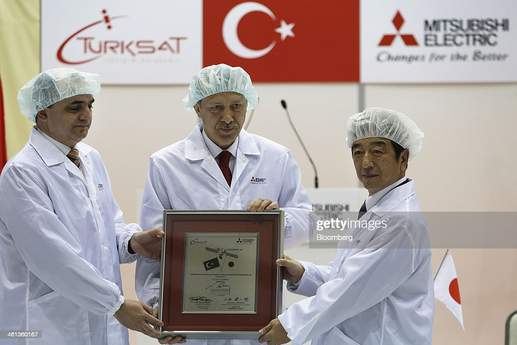 Ozkan Dalbay, chief executive officer of Turksat AS, left, <a gi-track='captionPersonalityLinkClicked' href=/galleries/search?phrase=Recep+Tayyip+Erdogan&family=editorial&specificpeople=213890 ng-click='$event.stopPropagation()'>Recep Tayyip Erdogan</a>, Turkey's prime minister, center, and Kenichiro Yamanishi, president and chief executive officer of Mitsubishi Electric Corp., pose with a memorial panel during a ceremony marking the shipment of Turksat AS's Turksat-4A communications satellite, manufactured by Mitsubishi Electric, at the company's satellite production facility at Kamakura Works in Kamakura, Kanagawa Prefecture, Japan, on Wednesday, Jan. 8, 2014. Turksat AS is Turkey's state-owned satellite operator. Photographer: Kiyoshi Ota/Bloomberg via Getty Images