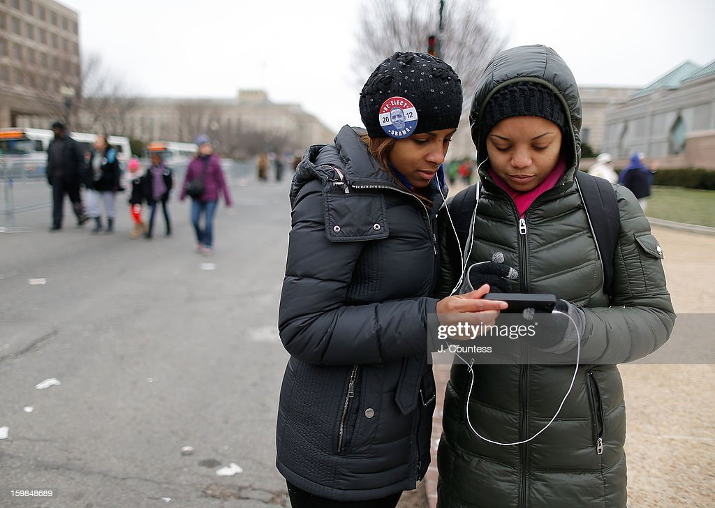 Ozzie of Philadelphia and Sophia of Washington DC listen to the Inauguration address by President Barack Obama on her iphone during the 57th United States Presidential Inauguration ceremony on January 21, 2013 in Washington, United States.