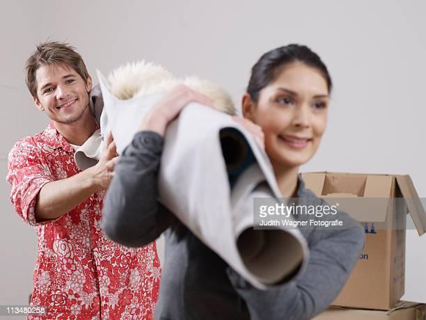 Paar mit Teppich auf Schulter bei Umzug