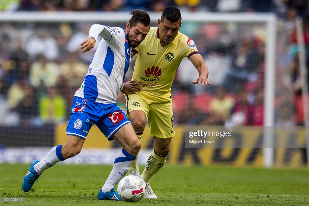 Pablo Aguilar of America fights for the ball with Fabio Santos of Puebla during the 1st round match between America and Puebla as part of the Clausura 2016 Liga MX at Azteca Stadium on January 09, 2016 in Mexico City, Mexico.