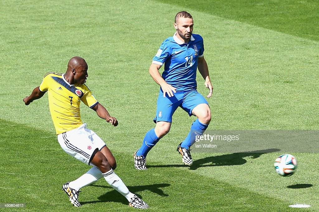 Pablo Armero of Colombia shoots and scores his team's first goal as Dimitris Salpingidis of Greece looks on during the 2014 FIFA World Cup Brazil Group C match between Colombia and Greece at Estadio Mineirao on June 14, 2014 in Belo Horizonte, Brazil.