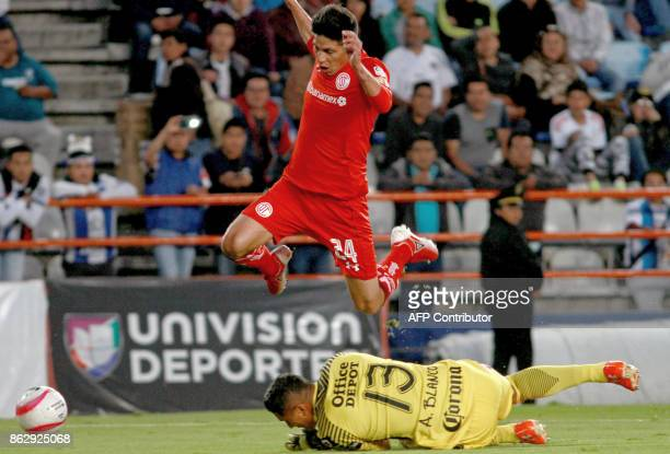 Pablo Barrientos of Toluca leaps over Pachuca's goalkeeper Alfonso Blanco during their Mexican Apertura tournament football match at the Hidalgo...