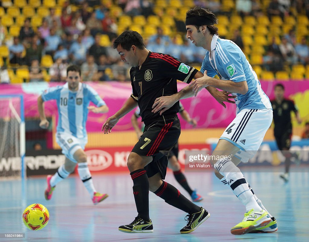 Pablo Belsito of Argentina tries to tackle Jorge Rodriguez of Mexico during the FIFA Futsal World Cup Thailand 2012 Group D match between Argentina...