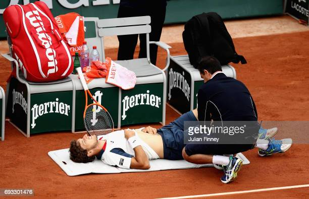 Pablo Carreno Busta of Spain is given treatment following an injury during mens singles quarter finals match against Rafael Nadal of Spain at Roland...