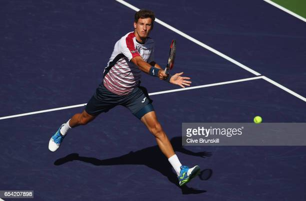 Pablo Carreno Busta of Spain plays a forehand volley against Pablo Cuevas of Uruguay in their quarter final match during day eleven of the BNP...